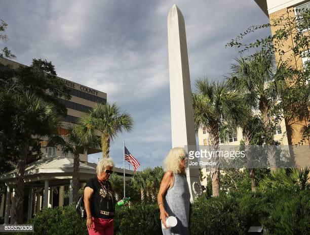 People walk past a granite obelisk commemorating Confederate Generals Stonewall Jackson Robert E Lee and Jefferson Davis and the memory of the...