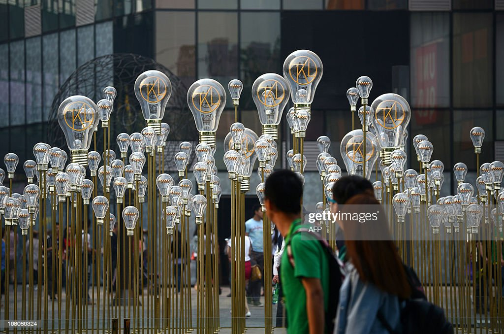 People walk past a group of bulbs on display in front of a shopping mall in Beijing on May 5, 2013. Manufacturing activity in China slowed slightly in April from the previous month, official data showed on May 1, in a sign of further weakness in the world's second-biggest economy.