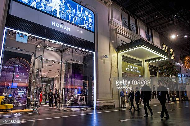 People walk past a Hogan clothing store and a Versace Collection store on The Boulevard at Studio City casino resort developed by Melco Crown...