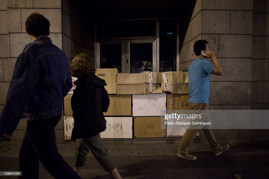 People walk past a homeles persons cardboard made wall in the front door of an abandoned bank office on October 11, 2012 in Madrid, Spain. Ratings agency Standard & Poor's has cut Spain's credit rating down to BBB-. The Spanish government has already introduced both spending cuts and tax rises in an attempt to ease their debt and reduce their high unemployment levels. Spanish Economy Minister Luis de Guindos maintains that his country will not need to ask for a bailout.