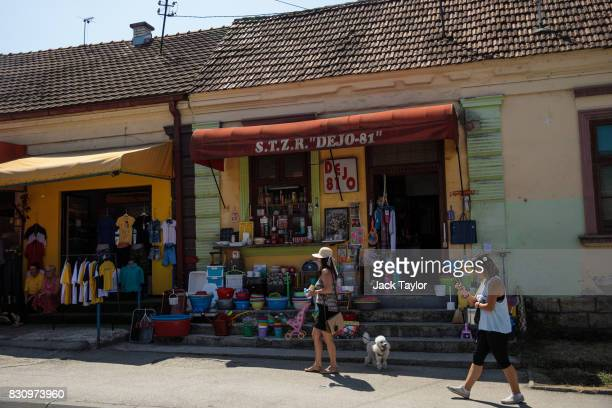 People walk past a homeware shop in the town centre during the Guca Trumpet Festival on August 10 2017 in Guca Serbia Thousands of revellers attend...