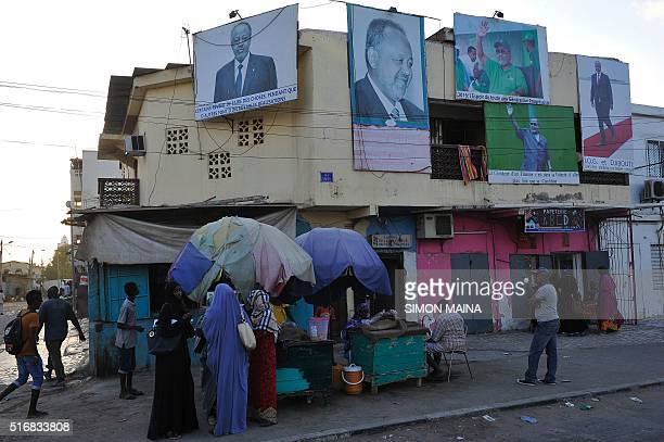 People walk past a house with billboards displaying portrait of incumbent Djibouti President Ismail Omar Guelleh in Djibouti on March 21 2016...