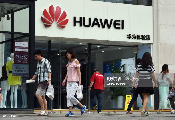 People walk past a Huawei store in Beijing on July 20 2015 Chinese telecoms equipment giant Huawei said on July 20 that revenue surged 30 percent...