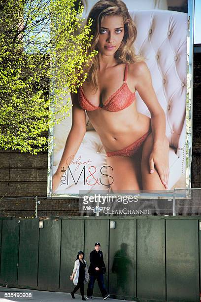 People walk past a huge advertising billboard poster for MS with Ana Beatriz Barros Lingerie or underwear for Marks and Spencer is big business and...