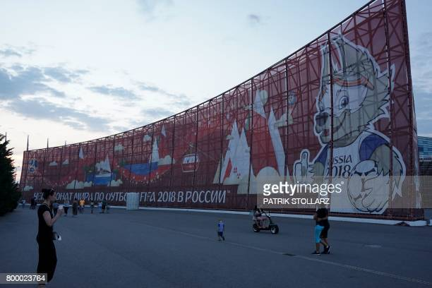 People walk past a huge World Cup 2018themed banner decorated with an image of Zabivaka the mascot for the football tournament in Sochi on June 22...