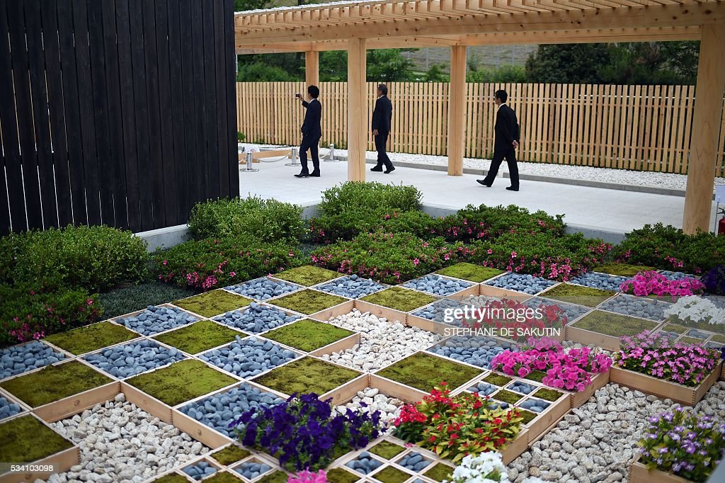 People walk past a Japanese garden at the International Media Centre in Ise city, Mie prefecture on May 25, 2016, ahead of the G7 summit. / AFP / STEPHANE