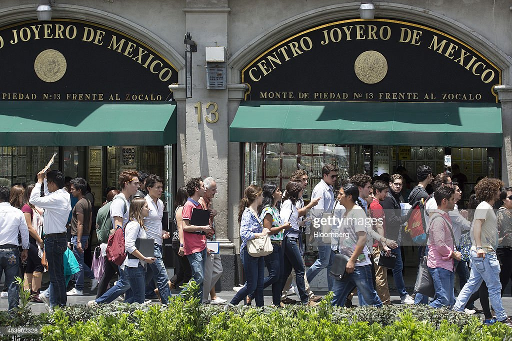People walk past a jewelry store in Mexico City, Mexico, on Thursday, Aug. 21, 2014. Mexican consumer prices rose more than analysts expected in the first half of August and the unemployment rate rose to 5.47 percent in July compared with 4.8 percent in June. Photographer: Susana Gonzalez/Bloomberg via Getty Images