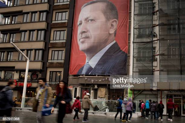 People walk past a large banner showing the portrait of Turkish President Recep Tayyip Erdogan in Taksim Square on March 13 2017 in Istanbul Turkey...