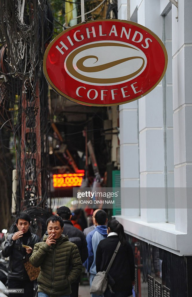 People walk past a locally run coffee shop in downtown Hanoi on January 3, 2013. Starbucks said on January 3 it would open its first store next month in Vietnam, seeking a foothold in the coffee-loving country as part of efforts to expand in Asia. AFP PHOTO / HOANG DINH Nam