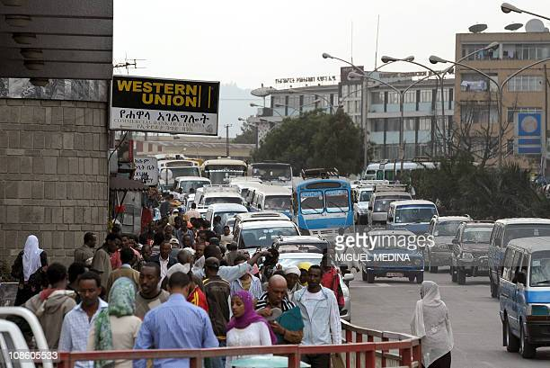 People walk past a logo of remittance bank Western Union on October 12 2010 in Addis Ababa AFP PHOTO / MIGUEL MEDINA