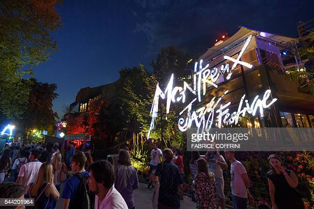 People walk past a logo of the Montreux Jazz Festival during its 50th edition on July 1 2016 in Montreux The 50th edition of the Montreux Jazz...