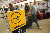 People walk past a Lufthansa checkin counter at Tegel Airport on March 19 2015 in Berlin Germany The union representing Lufthansa pilots Vereingung...