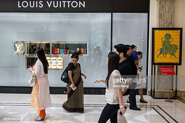 People walk past a LVMH Moet Hennessy Louis Vuitton SA store at the DLF Emporio shopping mall in New Delhi India on Thursday Oct 10 2013 Indian...