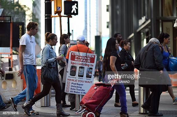 People walk past a man advertising cell phone repair in New York on October 17 2014 AFP PHOTO/Jewel Samad