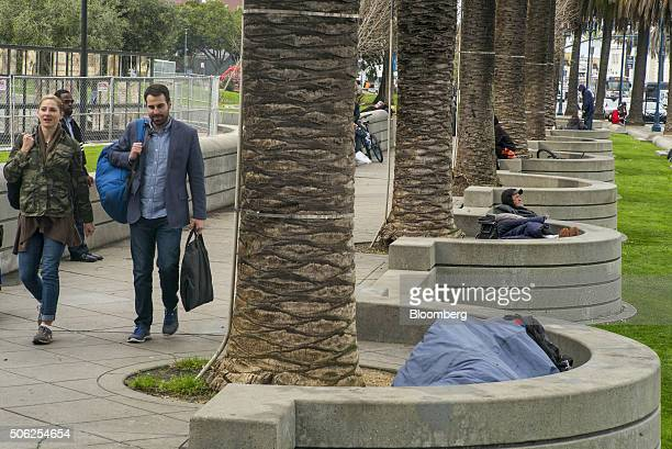 People walk past a man lying in a sleeping bag in Justin Herman Plaza in San Francisco California US on Thursday Jan 21 2016 San Francisco host city...
