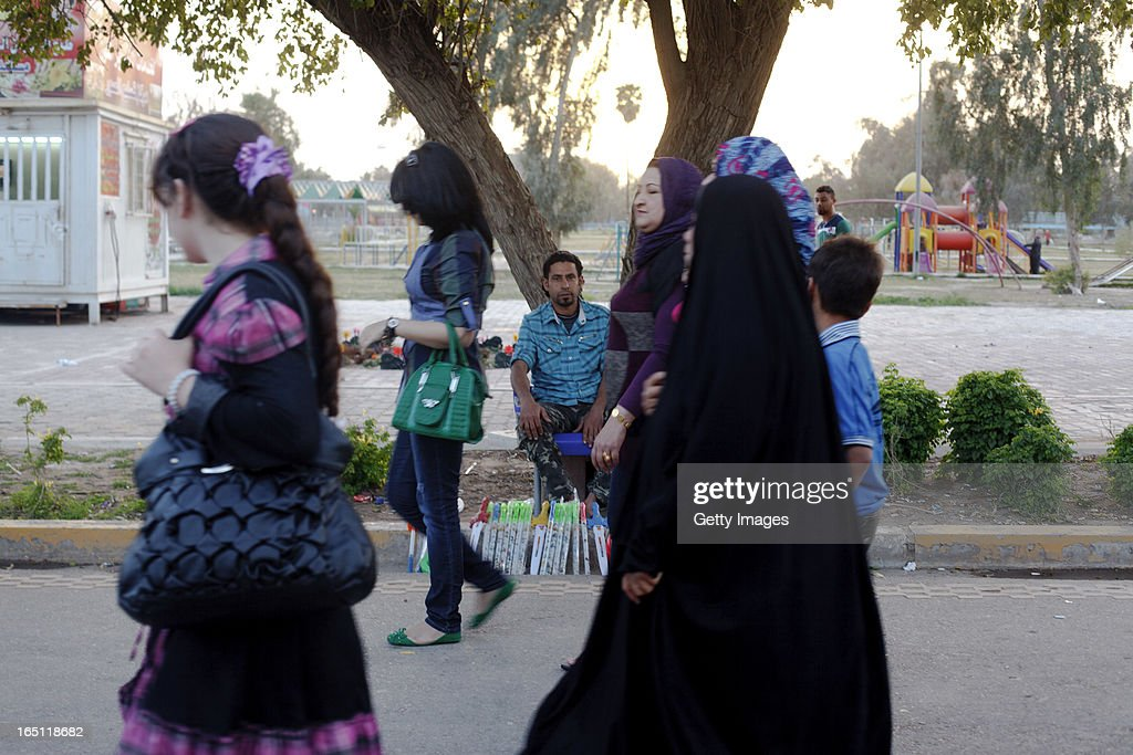 People walk past a man selling toys in Zawra Park, Baghdad. March 28, 2013 in Baghdad, Iraq. Ten years after the regime of Saddam Hussein was toppled from power, Baghdad continues to show the scars of the war. In vast areas, infrastructure is fractured and basic services are lacking, however, some areas of the capital are showing promising signs of recovery.