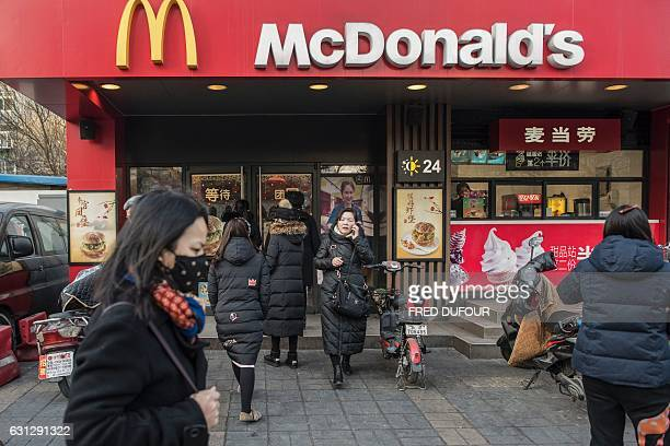 People walk past a McDonald's fast food restaurant in Beijing on January 9 2017 US fastfood giant McDonalds will sell a controlling stake in its...