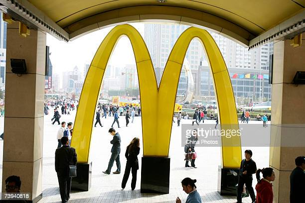People walk past a McDonald's restaurant on April 21 2007 in Shenyang of Liaoning Province China McDonald's and KFC both of which have been heavily...