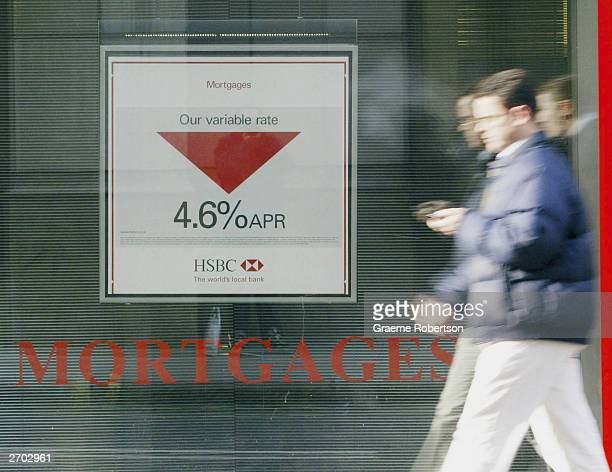 People walk past a mortgage advertisement November 6 2003 in London The Bank of England's Monetary Policy Committee has raised interest rates for the...