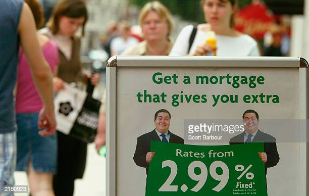 People walk past a mortgage advertising stand July 10 2003 in London England House price growth slowed in June but the property market remains well...