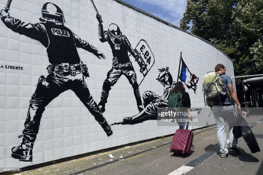 People walk past a mural by French artist Goin on June 27, 2016 in Grenoble, southeastern France. Mayor of Grenoble Eric Piolle (EELV) Monday invoked the freedom of expression after the controversy surrounding an urban art work deemed 'anti-police,' and created as part of a festival sponsored by the municipality. / AFP / PHILIPPE