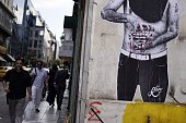 People walk past a mural depicting a person holding a bleeding Euro sign in central Athens on June 25 2015 Greek Prime Minister Alexis Tsipras...