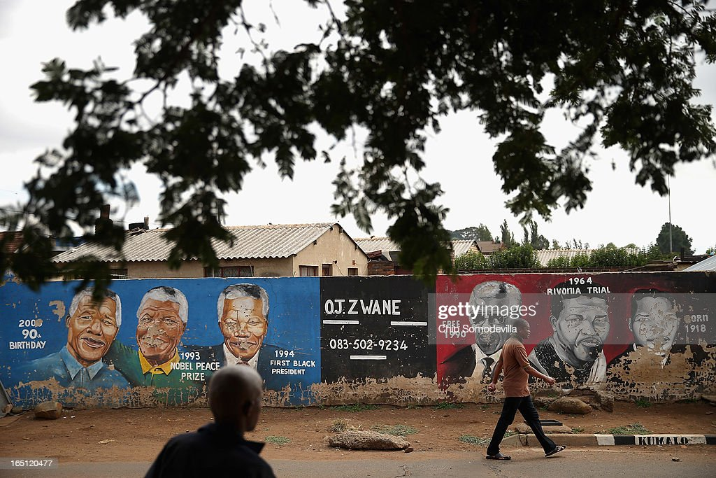 People walk past a mural depicting former South African President Nelson Mandela during different times in his life near the Regina Mundi Catholic Church in the Soweto area March 31, 2013 in Johannesburg, South Africa. A central gathering place during he anti-apartheid struggle, the church held prayers for Mandela, 94, who is in the hospital for the third time since December with lung problems. Referring to Mandela by clan name, Madiba, President Jacob Zuma said, 'We appeal to the people of South Africa and the world to pray for our beloved Madiba and his family and to keep them in their thoughts.' Mandela's lungs were damaged when he contracted tuberculosis during his 27 years in the infamous Robben Island prison. Mandela became the nation's first democratically elected president in 1994 following the end of apartheid.