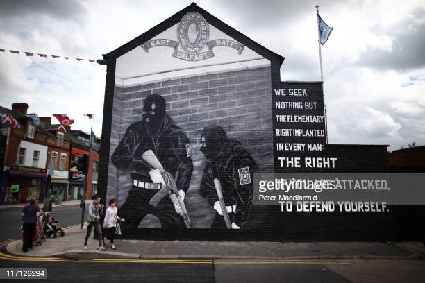 People walk past a mural depicting Ulster Volunteer Force gunmen in the mainly protestant area of East Belfast on June 23 2011 in Northern Ireland...