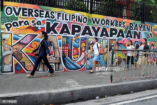 People walk past a mural honouring overseas Filipino workers in Manila on July 7 2014 The government estimates there are ten million overseas...