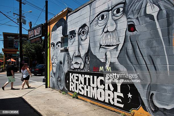 People walk past a mural of boxing legend Muhammad Ali US President Abraham Lincoln Kentucky Fried Chicken founder Colonel Harland David Sanders and...