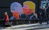 TOPSHOT People walk past a mural on a restaurant wall depicting US Presidential hopeful Donald Trump and Russian President Vladimir Putin greeting...