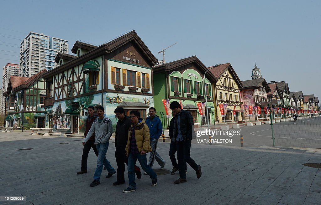 People walk past a new property development designed like a German village in Beijing, on March 22, 2013. China has been testing different measures to rein in it's booming property market. In Shanghai couples are flocking to divorce to use a loophole to avoid a new property sales tax and other laws see unmarried non-locals unable to buy apartments in large cities. AFP PHOTO/Mark RALSTON