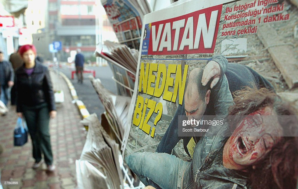 People walk past a newstand which displays pictures from the double bombings November 21, 2003 in Istanbul, Turkey. Bomb attacks on the British consulate and the HSBC bank headquarters have killed at least 27 people and left hundreds injured.