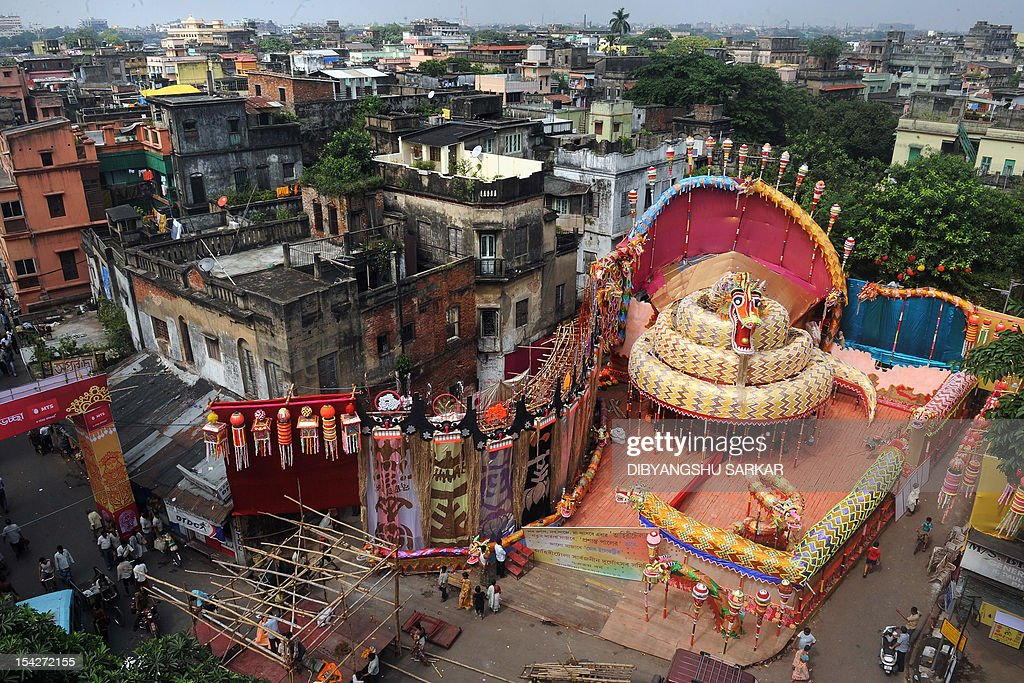 People walk past a Pandal (temporary worship place) made to worship Hindu goddess Durga built in a style inspired by Chinese art for the upcoming Hindu festival Durga Puja in Kolkata on October 17, 2012. The five-day period of worship of Durga, who is attributed as the destroyer of evil, commences on October 20.AFP PHOTO/Dibyangshu SARKAR