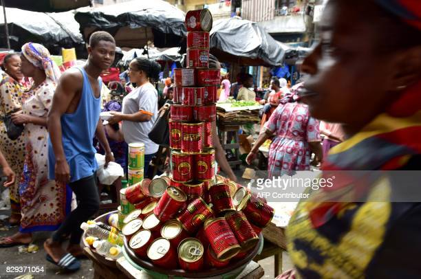 People walk past a pile of tinned tomatoes at the large market of Adjame a popular district of Abidjan on August 10 2017 The Ivorian government in a...