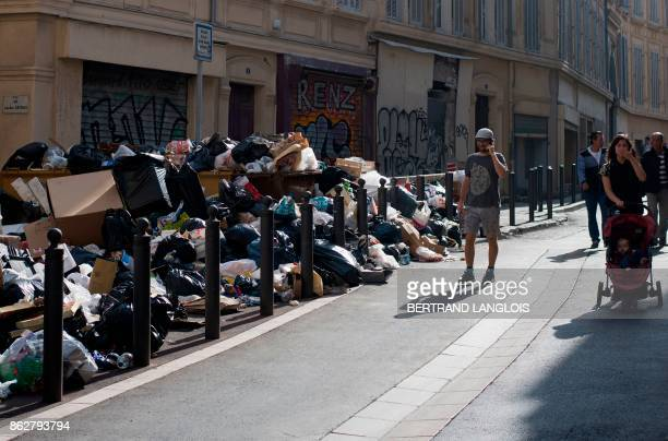 People walk past a pile of uncollected trash during a strike by refuse collectors on October 18 in Marseille southern France / AFP PHOTO / BERTRAND...
