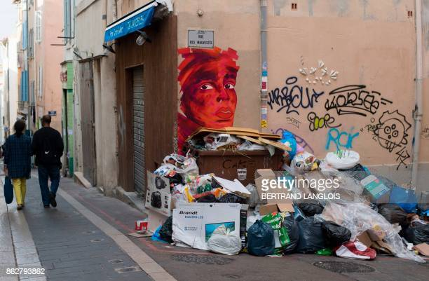 People walk past a pile of uncollected trash during a strike by refuse collectors on October 18 in the Panier district of Marseille southern France /...