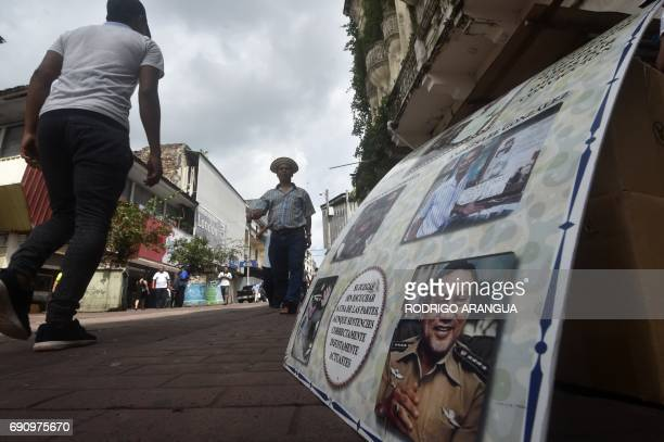 People walk past a placard with pictures of late former dictator Manuel Noriega who became Panama's de facto ruler in 1983 and was ousted from power...