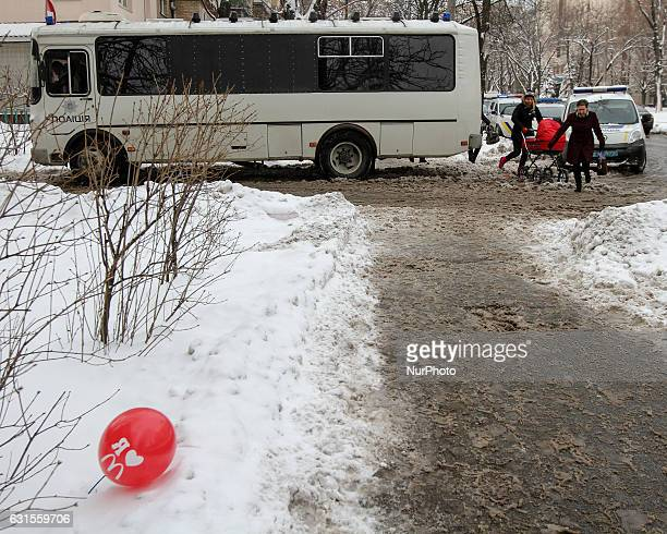A people walk past a police vehicles parked next to a Lukyanivske PTDC where a prisoner cut his ear to protest overnight into January 12 2017 in Kyiv...