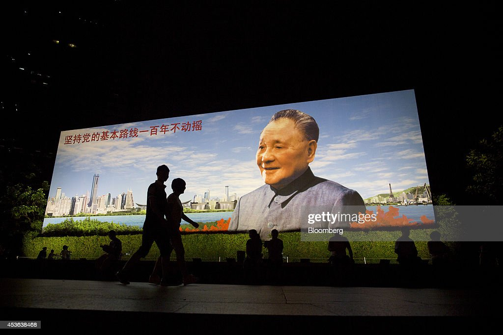 People walk past a portrait of China's former leader Deng Xiaoping that reads 'Persist with the Communist Partys fundamental path unwavering for one...