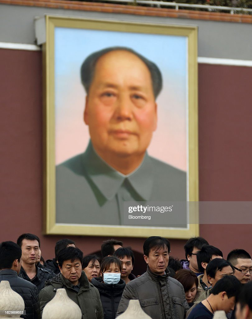 People walk past a portrait of former Chinese leader Mao Zedong at Tiananmen Gate in Beijing, China, on Saturday, March 2, 2013. Premier Wen Jiabao will this week formally announce this year's economic targets when he delivers his final work report to the National People's Congress, which begins on March 5. Photographer: Tomohiro Ohsumi/Bloomberg via Getty Images