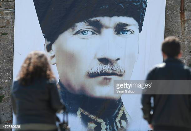 People walk past a portrait of Turkish Gallipoli division commander and founder of the first Turkish Republic Mustafa Kemal Ataturk on April 23 2015...
