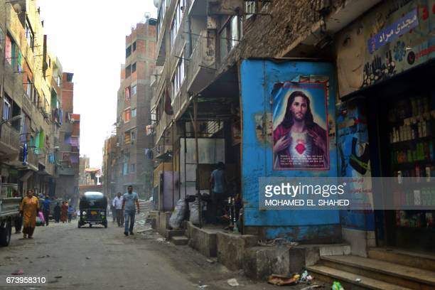 People walk past a poster bearing a portrait of Jesus Christ in the Zabalin area a day ahead of the visit of Pope Francis to the capital Cairo on...