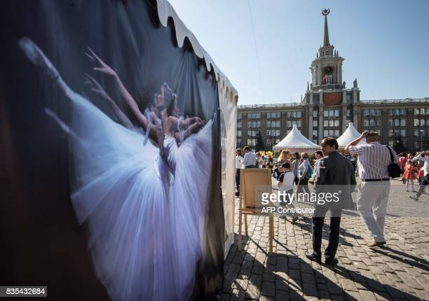 People walk past a poster depicting ballerinas on the main square in Yekaterinburg during the celebrations of the 294th anniversary of the city The...
