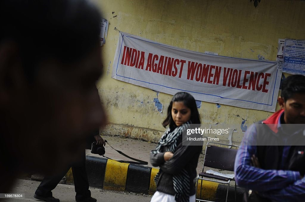 People walk past a poster during the protest against the alleged inaction by the Indian government regarding the gang rape of a 23-years old student in a bus a month ago, on January 16, 2013 in New Delhi, India. The bus rape has drawn protests and intense media attention. Rapes have become front-page news nearly every day across the country, with demands that police do more to protect women and that the courts treat sexual violence seriously.