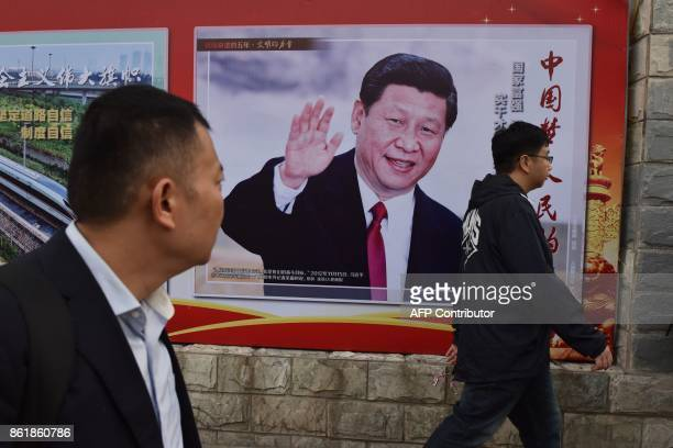 TOPSHOT People walk past a poster featuring Chinese President Xi Jinping with a slogan reading 'Chinese Dream People's Dream' beside a road in...