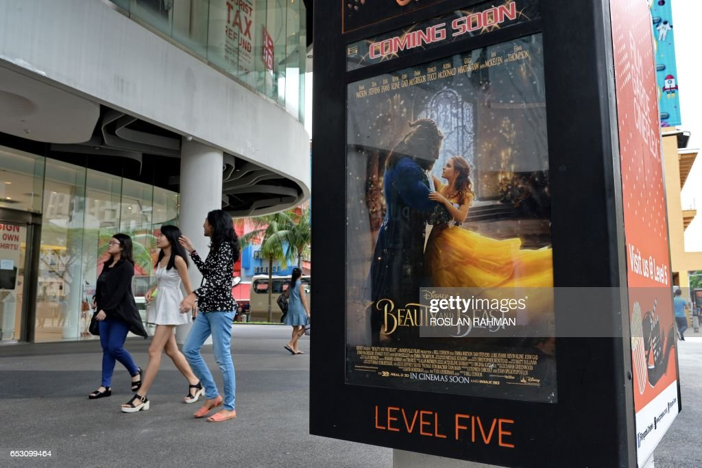 People walk past a poster for the film 'Beauty and the Beast' in Singapore on March 14, 2017. The film has come under fire from religious figures in Singapore, with Christian clergy attacking Disney for deviating from 'wholesome, mainstream values'. / AFP PHOTO / Roslan RAHMAN
