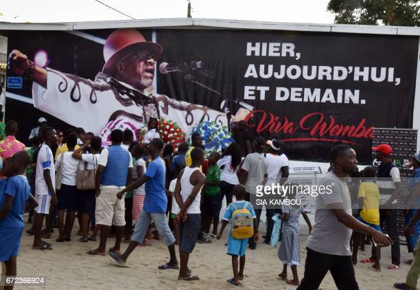 People walk past a poster in tribute to late Congolese rumba star Papa Wemba on April 24 2017 in Abidjan / AFP PHOTO / Sia KAMBOU