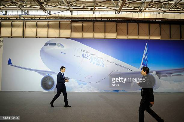 People walk past a poster of an Airbus A330 aircraft at the Tianjin Airport Economic Area on March 2 2016 in Tianjin China As the first Completion...
