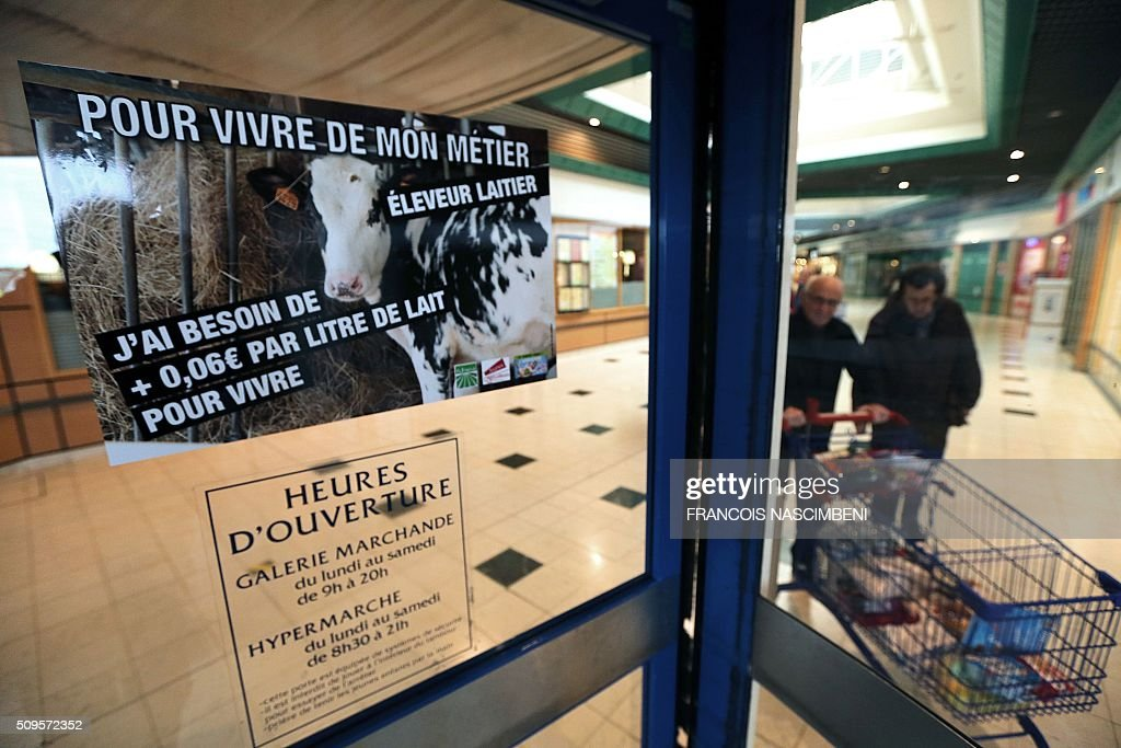 People walk past a poster reading 'I need to get paid 0,06 euros a liter of milk to live', put on a window of a Cora supermarket during a demonstration of French farmers who demand to be better paid by large-scale distributors, in Reims, on February 11, 2016. / AFP / FRANCOIS NASCIMBENI
